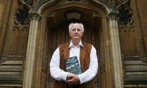 Philip Pullman poses with a copy of La Belle Sauvage.