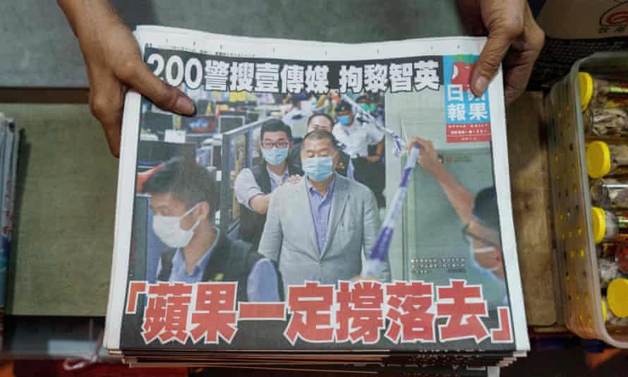 A vendor arranges fresh copies of the Apple Daily newspaper in Hong Kong showing a front page photo of its founder Jimmy Lai being escorted through the paper's newsroom by police following his arrest under the new national security law