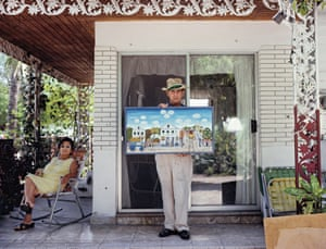 A folk artist on the veranda of his house in Key Westproudly displays a recent painting depicting an idealised view of old Key West, 1981