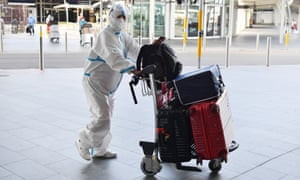An international traveller dressed in protective clothing arrives Sydney airport