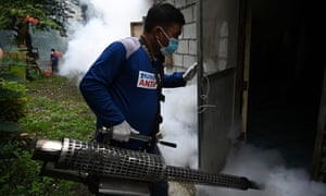 A municipal employee operates an insecticide fogging machine to kill mosquito larvae in a house in Antipolo, in the Philippine province of Rizal