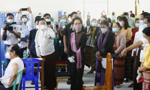 Myanmar leader Aung San Suu Kyi, center, inspects the vaccination processes to health workers at a hospital in Naypyitaw, Myanmar.