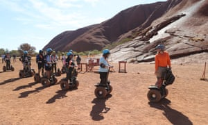 Tourists on segways pass the base of the climb at Uluru on the first full day of the climbing ban