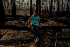 """Matthew Rijs takes a break along Jones Creek Road Wangarabell, after a day of carting hay and feeding cattle. The remote communty of Wangarabell, 45 kilometres from Mallacoota township was cut off for twelve days throughout the fires. Matthew cut his way through ravaged landscape to tend to his property, cattle and check on isolated neighbours, whose only choice in the end was to evacuate. """"I feel there has been a gross mis-management of the ecosystem and my hope for the future is better forest management."""""""