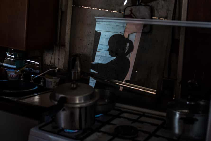 Mayra Castro, 37, prepares food in her improvised home in Petare. Her youngest daughter died of hunger when she was only one year old