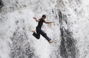 Rawang, Malaysia A man jumps off a cliff by the Serendah waterfall outside Kuala Lumpur