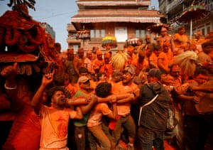Devotees carry a chariot while celebrating