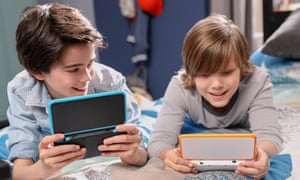 Nintendo 2DS XL portable games console in the hands of two boys.