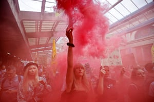 A climate activist from the Extinction Rebellion lets off a smoke bomb