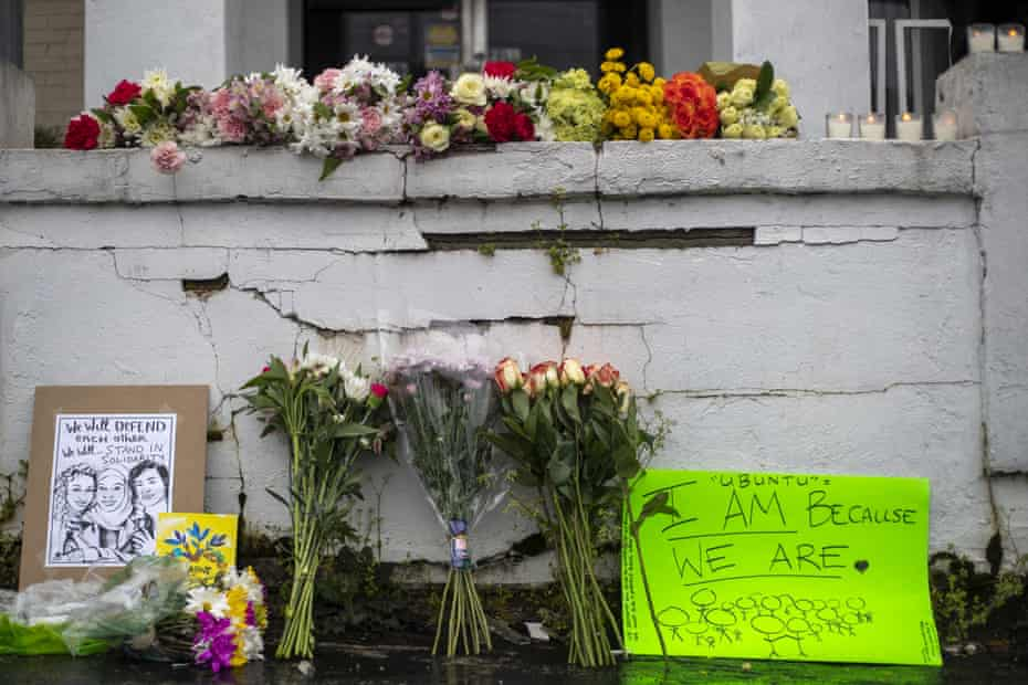 Flowers and signs are displayed at a makeshift memorial outside of the Gold Spa.