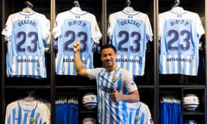 Shinji Okazaki poses in front of Málaga shirts with his name on in Japanese during his presentation on 31 July. But he was never to play for the troubled club.