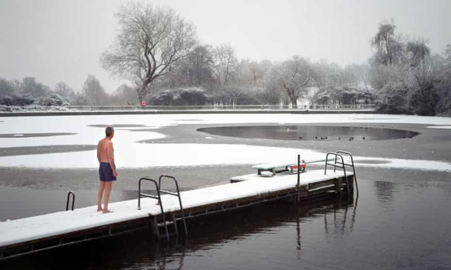 The men only Highgate Ponds, also known as Hampstead Ponds, in North London is a favourite spot for an early morning dip. As Britain is seized by the Big Freeze a few stalwarts go swimming in sub zero temperatures as the snow and ice turns Hampstead Heath in a winter wonderland. Swimming in freezing water can be dangerous to the uninitiated so people wishing to swim in the ponds during the winter are advised to acclimatise themselves to outdoor swimming. Advice from the Amateur Swimming Association is to start swimming outdoors in the summer and continue into winter preferably three or four times a week for short periods. Dangers are said to include numb freezing cold injury, hypothermia and sudden immersion syndrome (SIS). Photo by Michael Walter/Troika swim swimmers swimmer ice extreme sports
