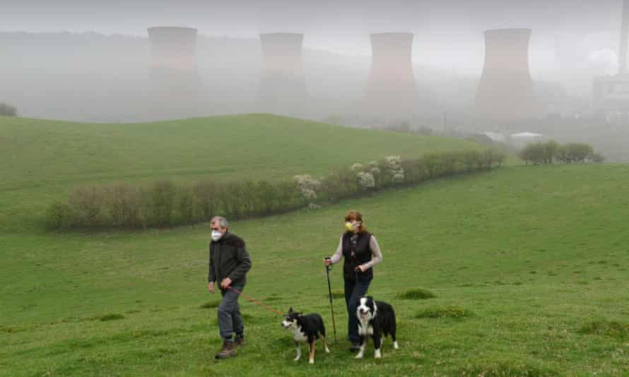 A couple wear smog masks while walking dogs near Ironbridge power station in Shropshire in 2014.