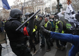 Police officers clash with demonstrators wearing yellow vests