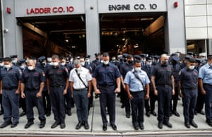New York City firefighters observe a moment of silence outside Ladder Co. 10, Engine Co. 10 in Manhattan.