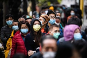People wearing facemasks as a preventative measure following a coronavirus outbreak which began in the Chinese city of Wuhan, line up to purchase face masks from a makeshift stall after queueing for hours following a registration process during which they were given a pre-sales ticket, in Hong Kong on February 5, 2020.