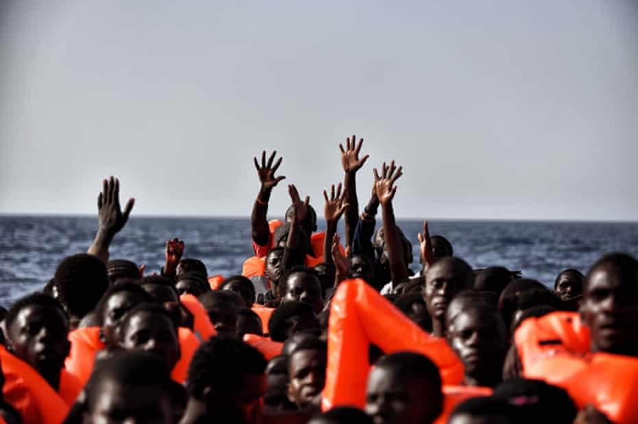 People wait to be rescued as they drift in the Mediterranean off the coast of Libya