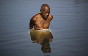 Visually-impaired Kartik Ram Sadhu, 67, a follower of Ramnami Samaj, and who has tattooed the name of the Hindu god Ram on his body, bathes in a pond in the village of Arjuni.