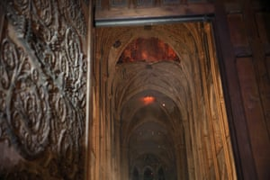 Smouldering flames are seen in the interior of Notre Dame cathedral in Paris