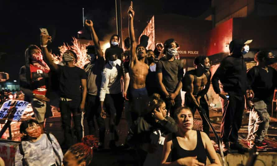 Protesters demonstrate outside of a burning Minneapolis third police precinct on Thursday.