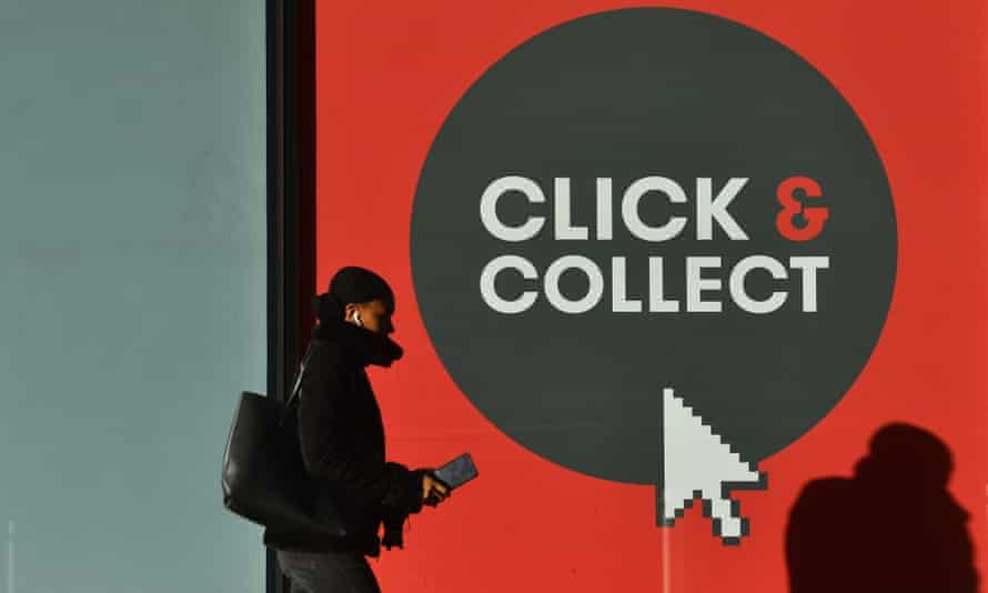 A woman walks past a click-and-collect sign in Birmingham