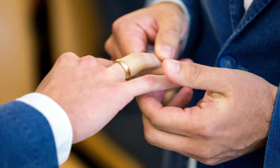 Two men exchange rings at a wedding ceremony in Munich.
