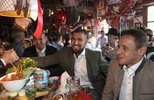 Vidal shakes the hand of a fellow Oktoberfest visitor as he sits with Arjen Robben and Rafinha