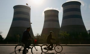 Local residents cycle past chimneys at a steel factory in Shenyang, in northeast China's Liaoning province.