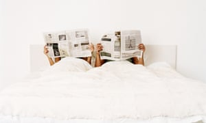 Couple lying in bed holding up newspapers