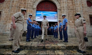 Members of the Colombian navy gather outside a church in Cartagena where the president, Juan Manuel Santos, will attend mass before signing a peace agreement with the Farc.