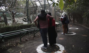 Visitors stand in designated white-circled visual cues to maintain social distancing as a preventive measure against the spread of the new coronavirus, during a visit to the zoo on the outskirts of Quito, in Guayllabamba, Ecuador.