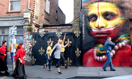 Dancers who are part of Melanie Manchot's commission for Art Night 2017 pass a mural by Dale Grimshaw in London.