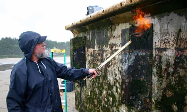A volunteer burns marine organisms off a Japanese pier on Agate Beach, Newport, Oregon