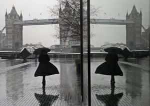 A woman is reflected in a window as she braves wind and rain while walking towards Tower Bridge during England's third national lockdown.