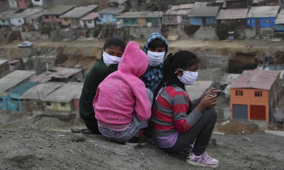 Children wearing masks sit on a hill in Puente Piedra shantytown on the outskirts of Lima.