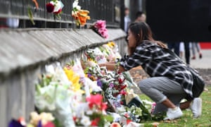 People gather to lay flowers outside the Botanic Gardens in Christchurch