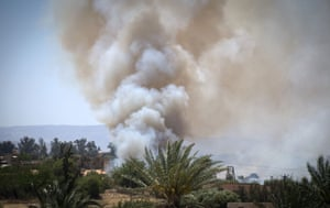A pall of smoke rises above buildings in Espiaa