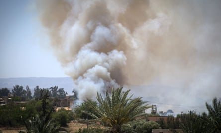 Heavy smoke rises above buildings in Espiaa, about 40km south of Tripoli