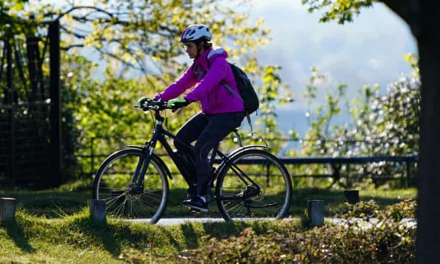 A cyclist on an e-bike rides through Richmond Park in London