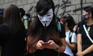 A hong kong protester wearing a Guy Fawkes mask uses her mobile phone