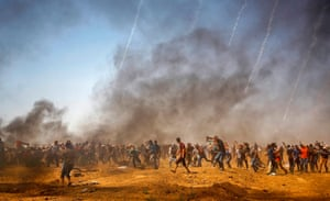 Palestinian protesters run for cover as teargas is fired by Israeli troops during a protest at the Israel-Gaza border