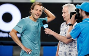 A relieved looking Lucas Pouille is interviewed for television by former champion John McEnroe.
