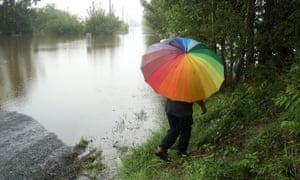 A man with a multi-coloured umbrella walks on the waters edge of the flooded Hawkesbury river at Inalls lane in Richmond on 23 March 2021 in Sydney.