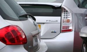 A Toyota Prius hybrid car behind a Toyota Auris at a car dealer