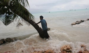 Pita Meanke, of Betio village, stands beside a tree and watches as the sea crashes through his family's sea wall and on to his property