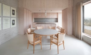 The dining area of Tŷ Bywyd (Life House), taken during the day. Pale furniture around a pale table and kitchen units.