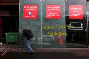 A man sweeps outside a vandalised store