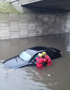 Firefighters rescuing a person from a car in a flooded street in Blackpool
