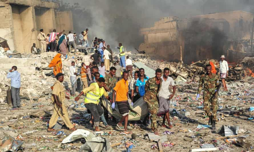 Men and Somalian soldiers rescue victims on the site of the explosion of the truck bomb in the centre of Mogadishu.