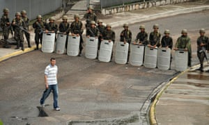 A pedestrian walks past a row of soldiers near the presidential palace following a coup d'etat that saw President Manuel Zelaya ousted in Tegucigalpa on 28 June 2009.